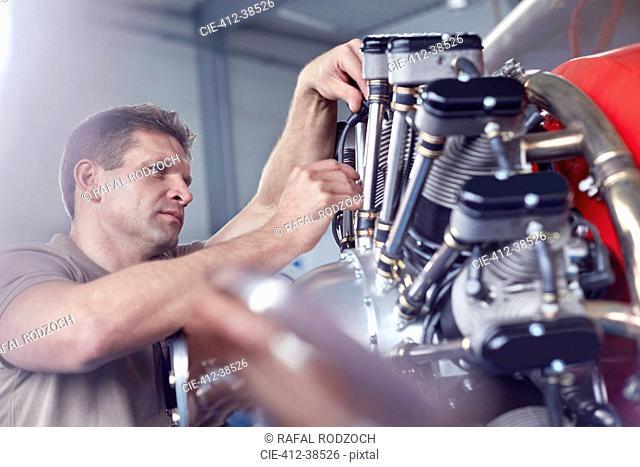Male airplane mechanic repairing propellor
