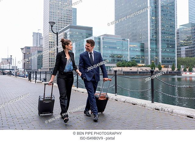 Businessman and businesswoman pulling trolley luggage, Canary Wharf, London, UK