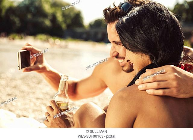 Couple in love taking selfie on the beach