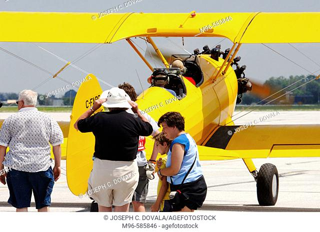 Stearman biplane takes off with charter passenger during airshow. Windsor, Canada