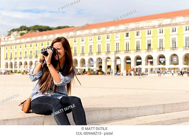 Young female tourist photographing in Rossio Square, Lisbon, Portugal