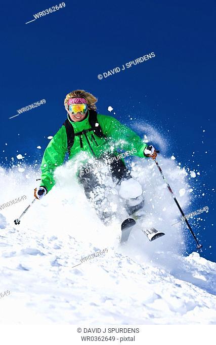 Happy female skier blasting through fresh powder snow