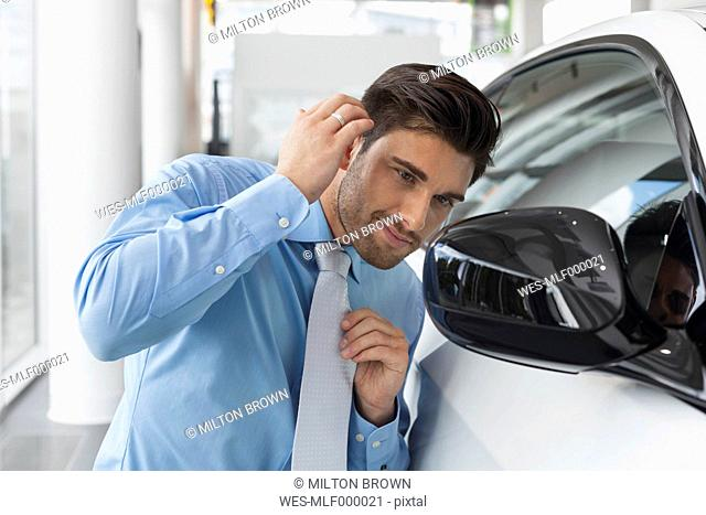 At the car dealer, Salesman checking his look in wing mirror