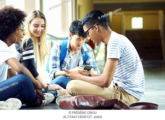 Friends sitting together on floor of school corridor between classes