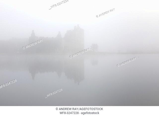 Kilchurn Castle reflected on the still surface of Loch Awe on a misty moring