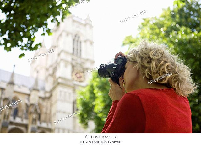 A middle-aged woman photographing Westminster Abbey