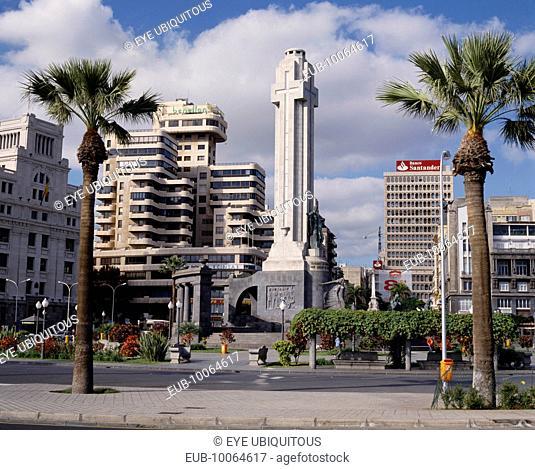 Santa Cruz. Plaza de Espana and Civil War Monument of grey stone and a tall cross with city skyline behind