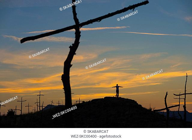 Spain, Manresa, woman standing on hill, burned forest with symbols of crosses in the morning
