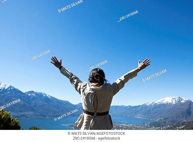 Woman with raised arms enjoy panoramic view over alpine lake Maggiore with snow-capped mountains in a sunny day with blue sky in Ticino, Switzerland