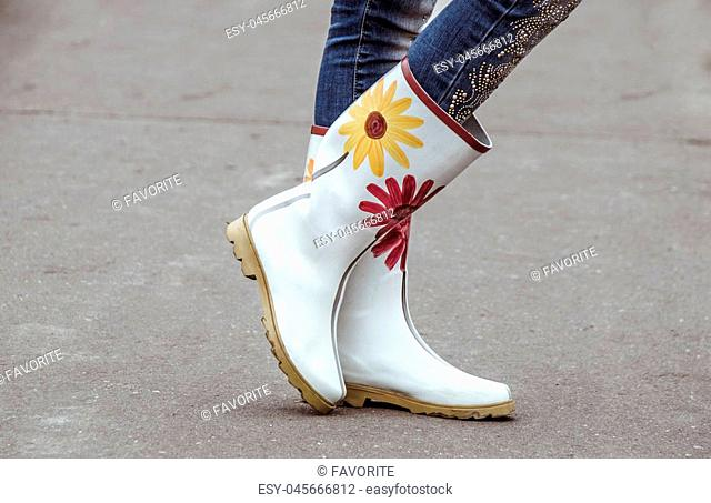 Woman in beautiful gum boots with flowers outdoors
