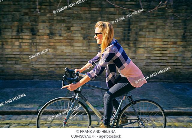Side view of mid adult woman cycling on bicycle