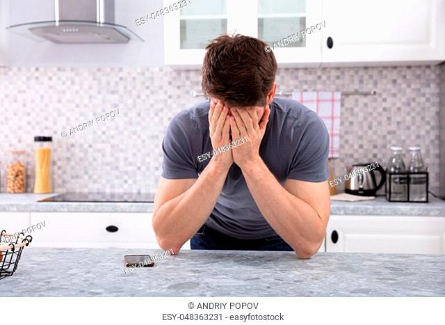 Frustrated Man Covering His Face With Two Hand Sitting In Kitchen