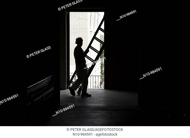 Worker carrying a ladder in a dark building