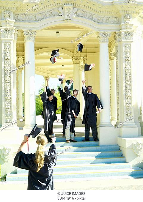 Graduates throwing caps in air in celebration