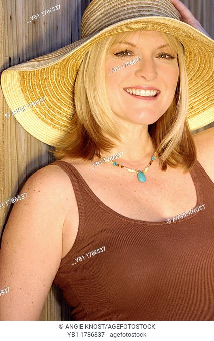 Attractive blond woman in her 40s , smiling and wearing a sunhat  She is outside in bright sunlight