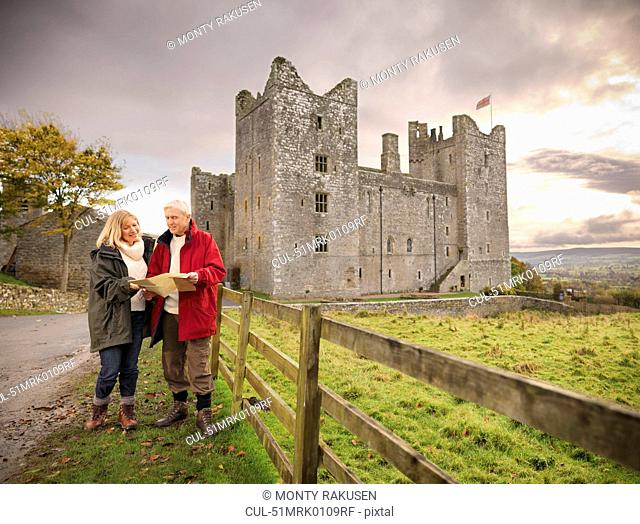 Older couple reading map by castle