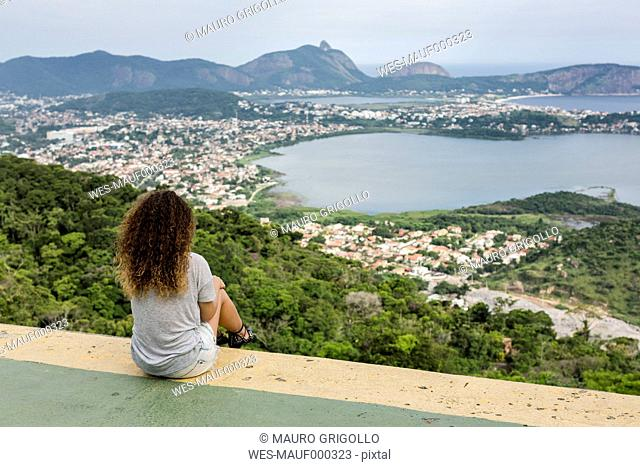 Brazil, woman sitting on a viewpoint in Rio de Janeiro