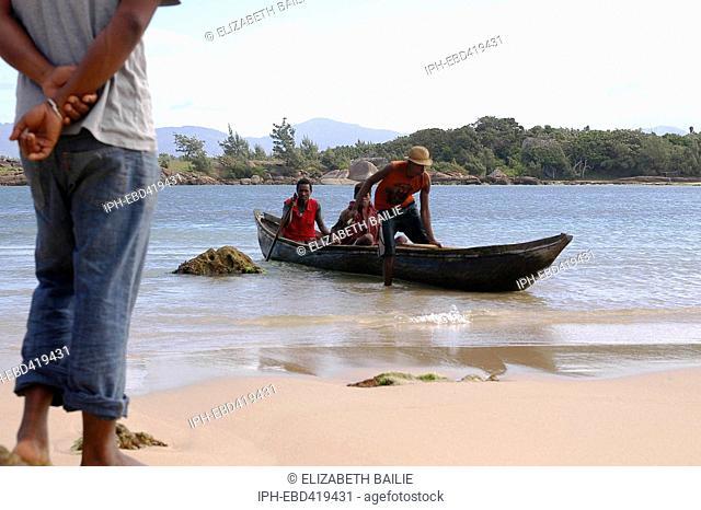 Madagascar Anosy region Lokaro Beach with fishermen in canoe coming ashore
