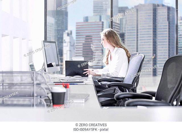 Businesswoman writing notes and using computer in front of office window