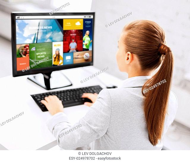business, people, technology, media and education concept - businesswoman or student girl with internet page on computer screen sitting at office table