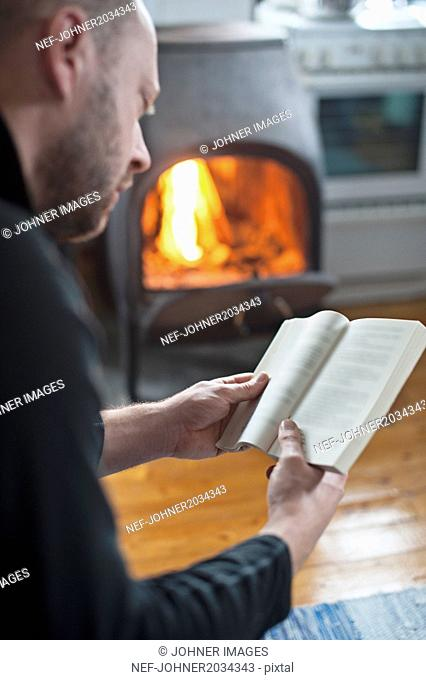 Man reading book, fireplace on background