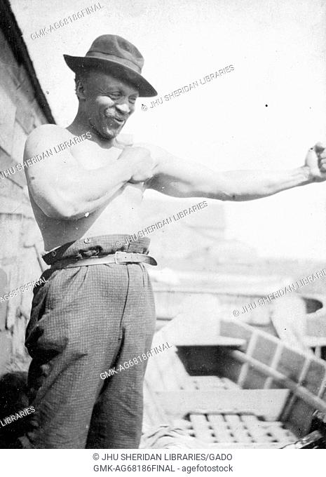 Three-quarter portrait of shirtless African American man, trousers worn high secured by belt, arms outstretched as if boxing, wearing a hat