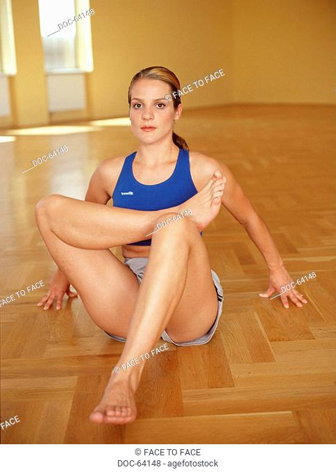 Young adult woman does doing sports practices in a hall - in the Seated