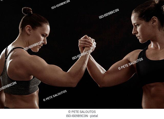 Muscular women gripping hands