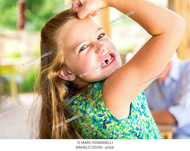 Caucasian girl showing missing teeth and flexing biceps