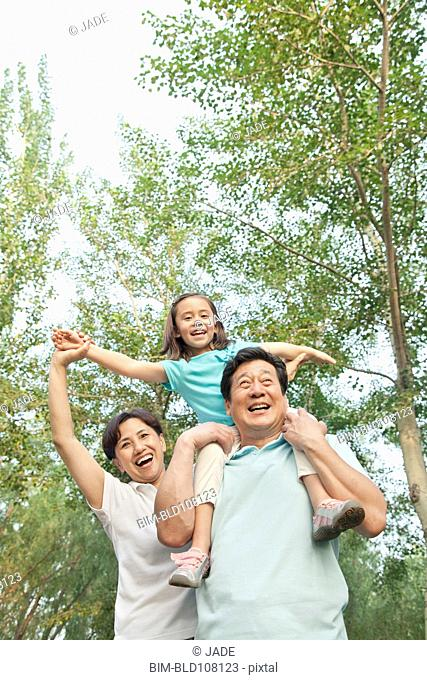 Chinese grandfather carrying granddaughter on shoulders