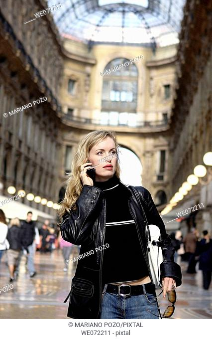 29 year old woman using cell phone in Galleria Vittorio Emanuelle II, Piazza del Duomo, Milan. Lombardy, Italy