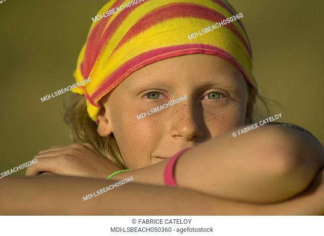 Portrait of a little girl with a yellow and red bandana on the beach