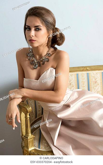 elegant brunette girl with rich style posing with elegant pink dress and precious necklace on old sofa in indoor portrait