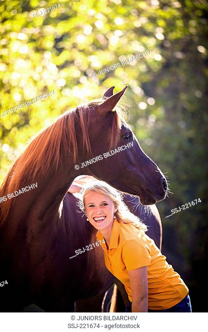 Arabian Horse. Portrait of chestnut mare and girl. Germany