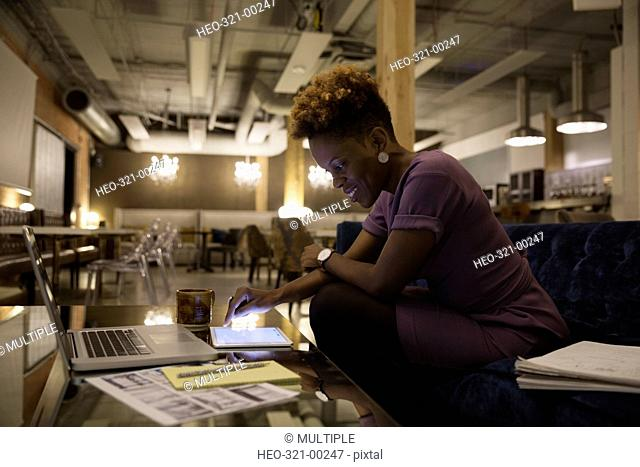 Female designer working late using digital tablet in office