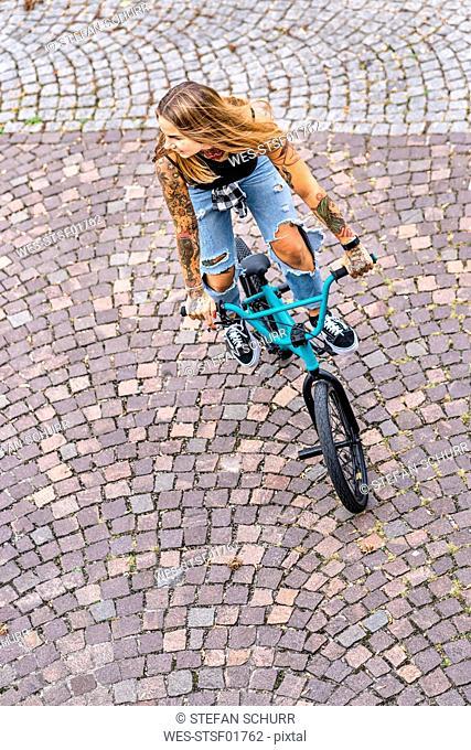 Young woman riding her BMX bike