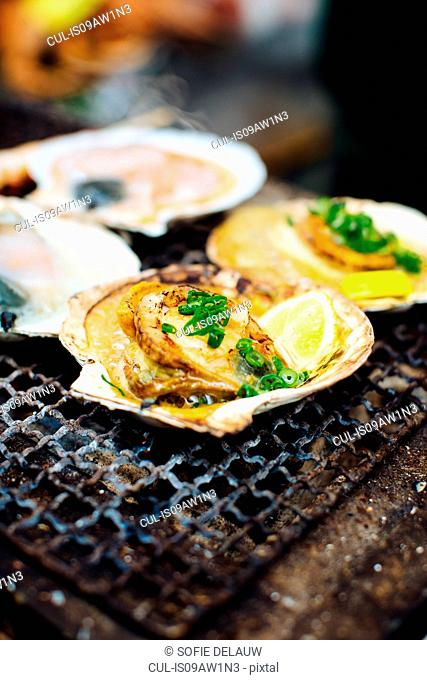 Food stall with grilled scallops, lemon and spring onions, Japan