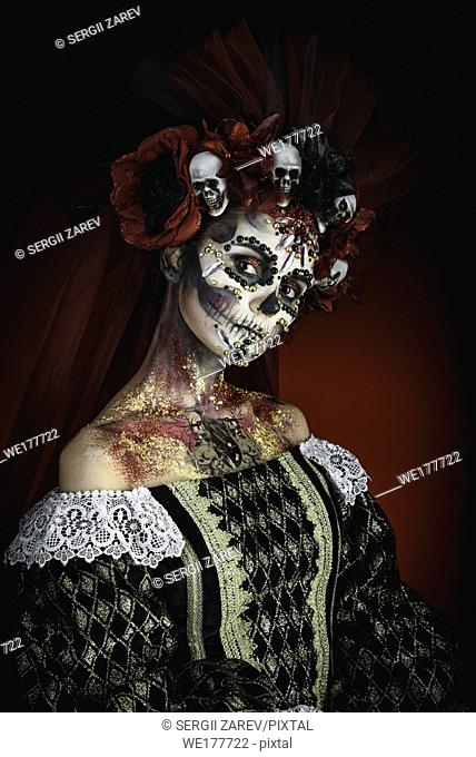 Santa Muerte Young Girl with Artistic Halloween Makeup and with Sculls in her Hair