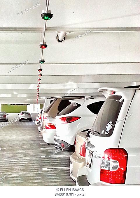 Row of white cars in a parking garage with red and green lights indicating whether a parking spot is available based on sensor technology