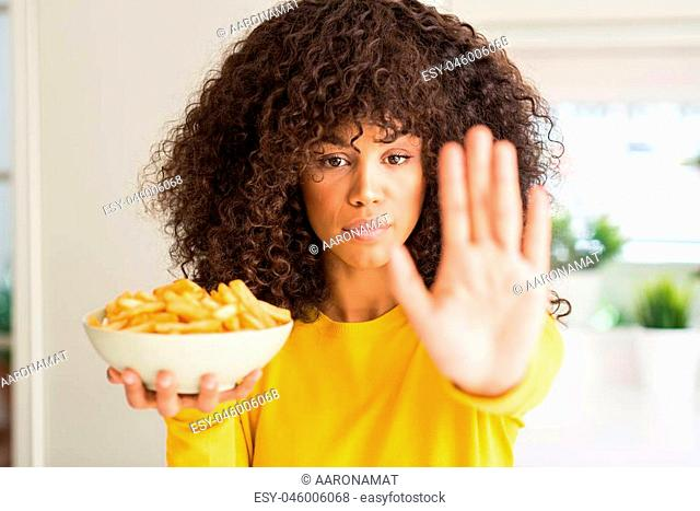 African american woman holding a plate with potato chips at home with open hand doing stop sign with serious and confident expression, defense gesture