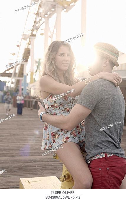 Young couple hugging on Santa Monica pier, California, USA