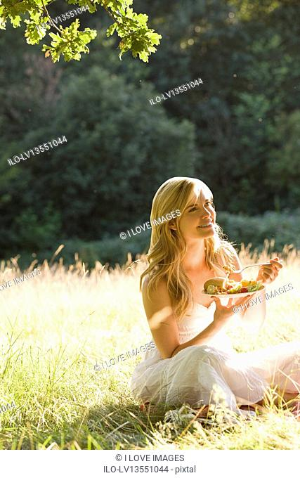 A young woman sitting on the grass, eating