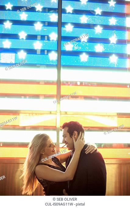 Romantic young couple and neon american flag, New York City, USA