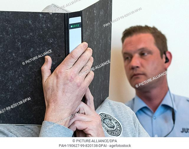 27 June 2019, North Rhine-Westphalia, Detmold: The defendant Andreas V. hides his face behind a file. For many years, children on a camping site in Lügde