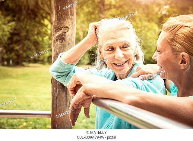 Women in park leaning against metal bar face to face smiling