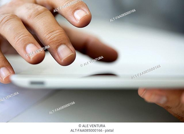 Man using touch screen on digital tablet, cropped