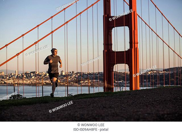 Young man out running near golden gate bridge