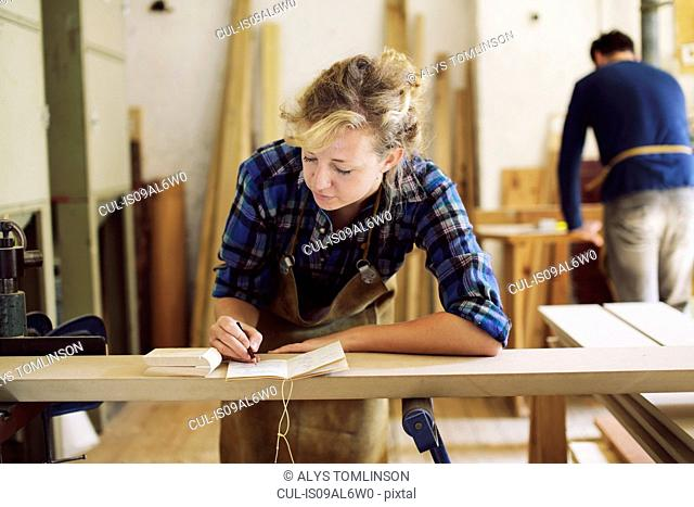 Young craftswoman making notes in pipe organ workshop