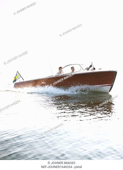 Two men driving motorboat