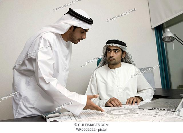 Two Arab businessmen discussing at work